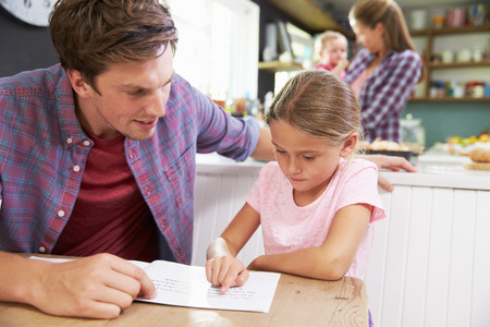 literacy: Father Reading Book With Daughter At Kitchen Table