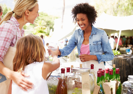 business owner: Woman Selling Soft Drinks At Farmers Market Stall Stock Photo
