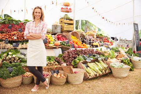 농민 신선 식품 시장에서 여성 스톨 홀더 스톡 콘텐츠