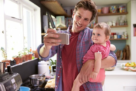 whilst: Father Cooks Meal Whilst Holding Young Daughter