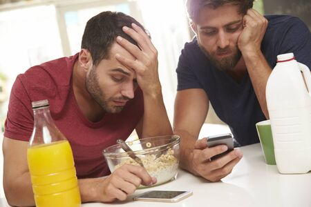 and the horizontal man: Male Friends Checking Phones After Sending Text Whilst Drunk Stock Photo