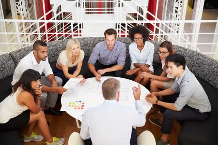 reunion de trabajo: Grupo de compañeros de trabajo que tienen reunión en un pasillo de la oficina Foto de archivo