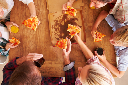 overhead view: Friends sharing a pizza together, overhead view