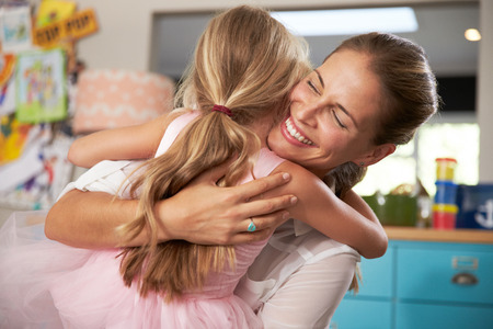 two women hugging: Daughter Hugging Mother Returning From Work Stock Photo