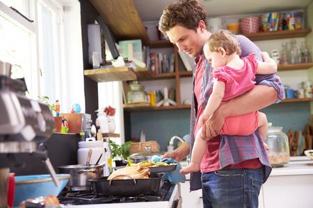 niños cocinando: Padre Cocinar la comida mientras Holding Hija En Cocina