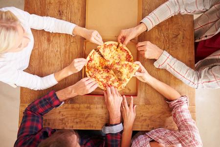 pizza: Amigos que comparten una pizza juntos, vista aérea Foto de archivo