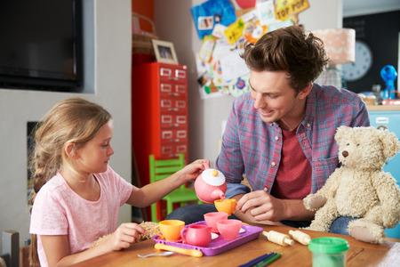 fiesta familiar: Padre que juega al juego con la hija y juguetes en Dormitorio