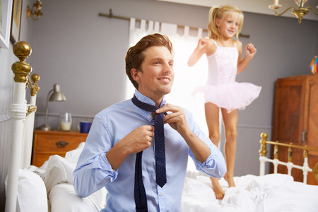 getting ready: Father Dresses For Work As Daughter Plays In Bedroom Stock Photo