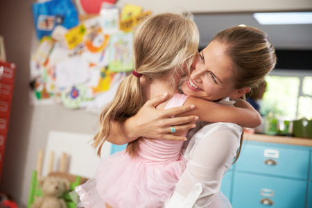 parent child: Daughter Hugging Mother Returning From Work Stock Photo