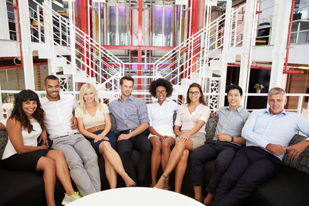 gente sentada: Grupo de compa�eros de trabajo sentado en un pasillo de la oficina