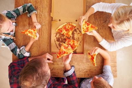 comida rapida: Familia comiendo pizza juntos, vista aérea Foto de archivo