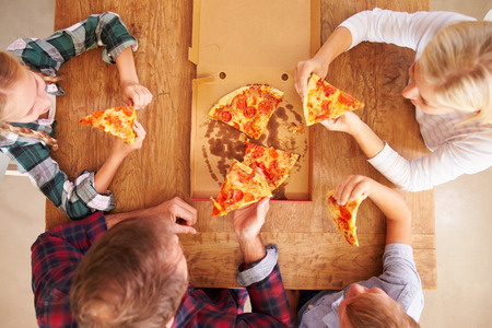 fast eat: Family eating pizza together, overhead view