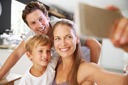 niños desayunando: Familia que presenta para selfie En Mesa de desayuno
