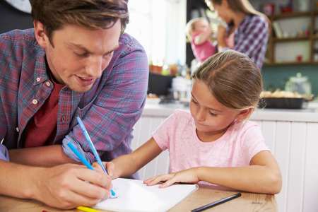 family life: Father Helping Daughter To Draw Picture At Kitchen Table