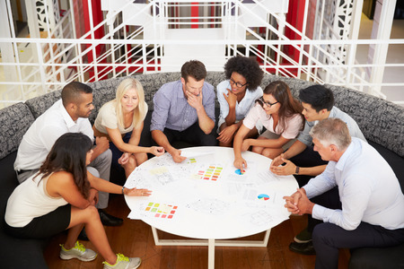 small business team: Group of work colleagues having meeting in an office lobby