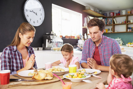 praying people: Family Saying Prayer Before Eating Meal In Kitchen Together