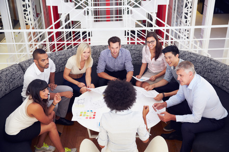 business relationship: Group of work colleagues having meeting in an office lobby