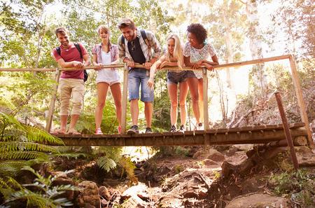 Group Of Friends On Walk Crossing Wooden Bridge In Forest Stock fotó