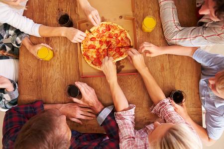 personas comiendo: Amigos que comparten una pizza juntos, vista aérea Foto de archivo