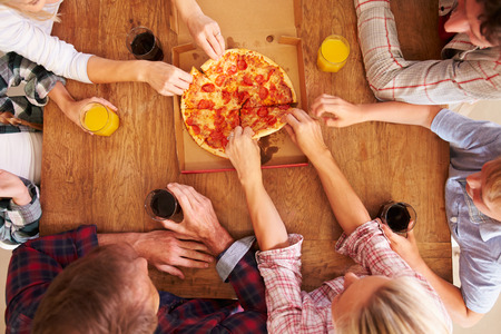 eating pizza: Friends sharing a pizza together, overhead view