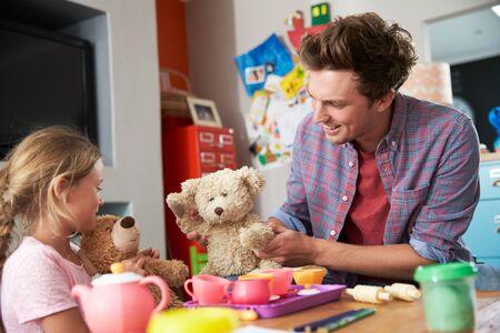 familias felices: Padre que juega al juego con la hija y juguetes en Dormitorio