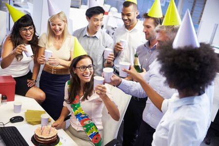 asian adult: Celebrating a colleagues birthday in the office Stock Photo
