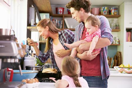 一緒にキッチンで食事を調理している家族
