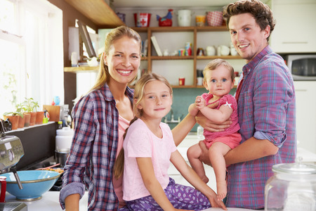 11 years: Portrait Of Family Cooking Meal In Kitchen Together