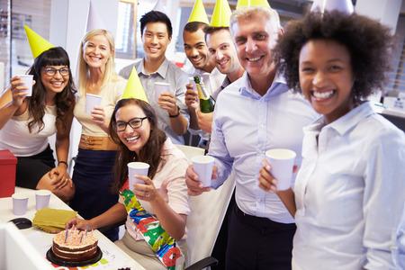 sorpresa: Celebrando el cumpleaños de un colega en la oficina Foto de archivo