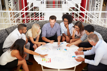business strategy: Group of work colleagues having meeting in an office lobby