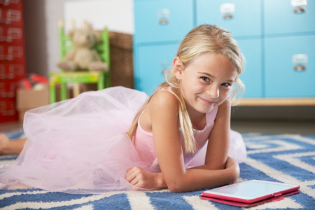 7 years old: Pretty Girl Lying On Floor Of Bedroom With Digital Tablet
