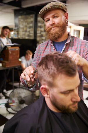 barber chair: Portrait Of Male Barber Giving Client Haircut In Shop