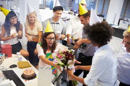 adult birthday: Celebrating a colleagues birthday in the office Stock Photo