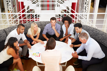 sit: Group of work colleagues having meeting in an office lobby