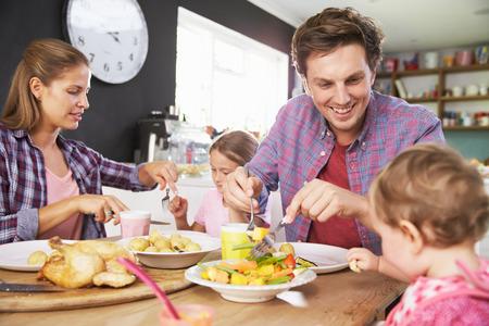 Familia que come la comida en cocina Juntos