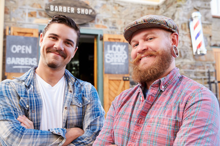 horizontal haircut: Portrait Of Two Hipster Barbers Standing Outside Shop