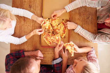 binge: Friends sharing a pizza together, overhead view
