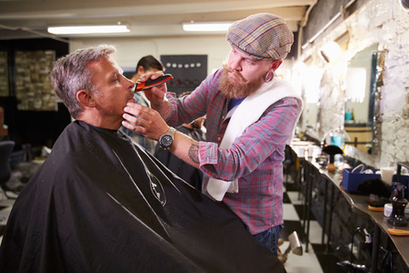 hairdressers: Male Barber Giving Client Shave In Shop