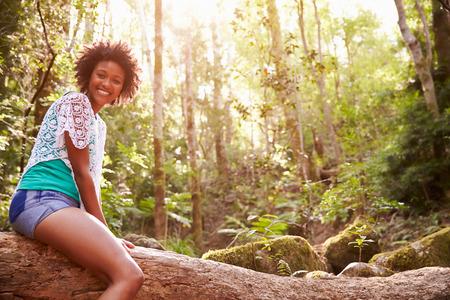Portrait d'une femme assise sur tronc d'arbre En Forêt Banque d'images - 41461789