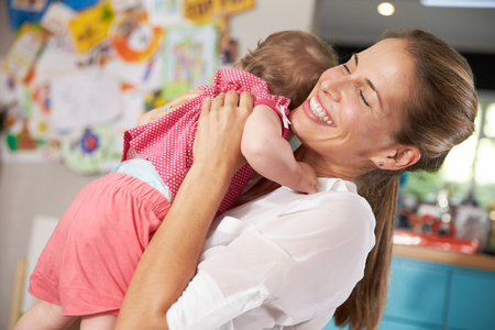 returning: Mother Returning From Work Hugging Young Daughter