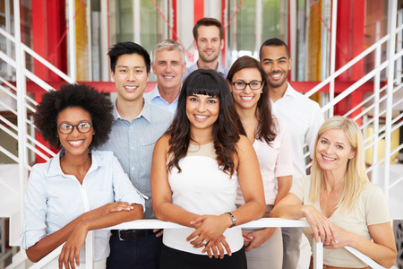 young man smiling: Group of work colleagues standing in an office lobby Stock Photo