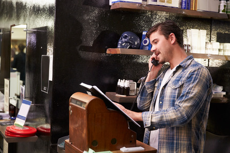 male beauty: Male Barber Standing By Cash Register Taking Booking