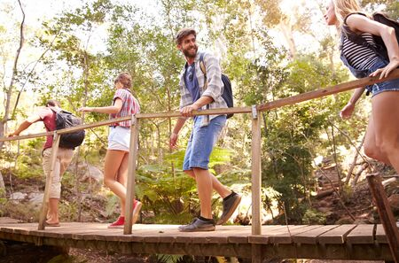Group Of Friends On Walk Crossing Wooden Bridge In Forest photo