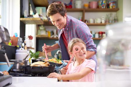 niños cocinando: Hija de ayuda Padre para cocinar la comida en cocina