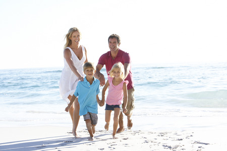 7 year old girl: Young Family Running Along Sandy Beach On Holiday Stock Photo