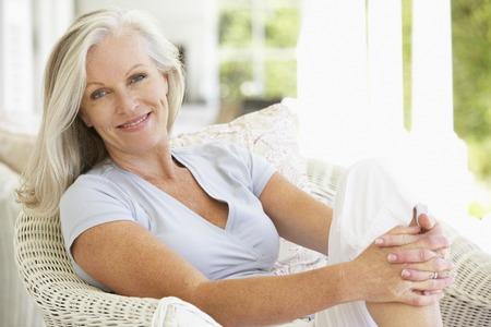 personas sentadas: Mujer mayor que se sienta afuera