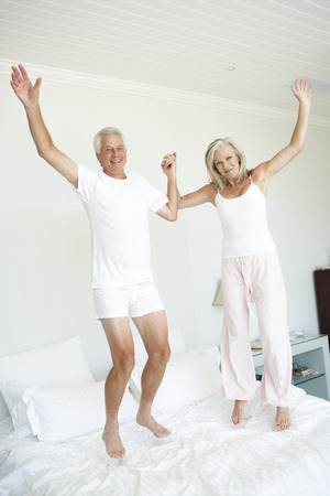 pijama: Pareja mayor que salta en cama