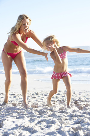 swimming costume: Mother And Daughter Running Along Beach Together Wearing Swimming Costume