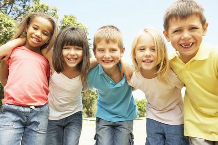 niños felices: Grupo de niños sonrientes que se relajan en el parque
