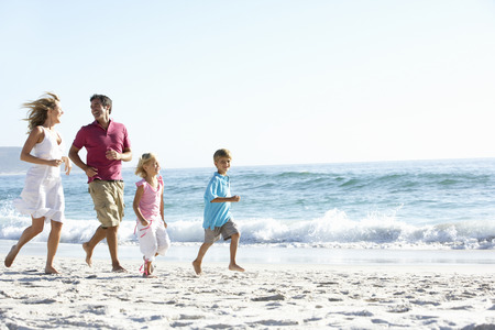 Young Family Running Along Sandy Beach On Holiday Foto de archivo